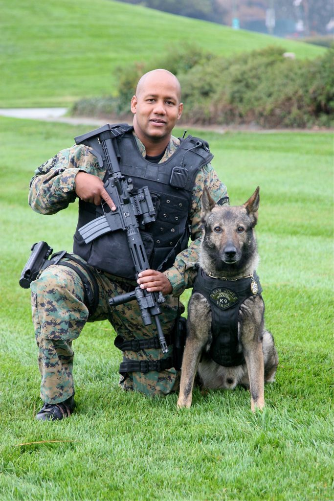 Police officer in bullet proof vest with rifle and a Belgian Malinois Police Dog